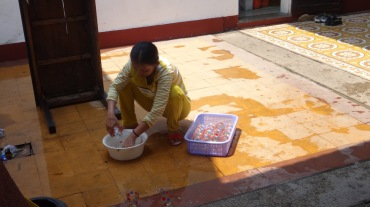 Women cleaning glasses in plain bucket of water